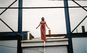 An image of a woman standing on the edge of a structure.