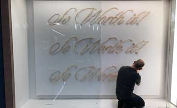 A man kneels behind a glass panel. He is working on embroidering a large art installation that repeats the text