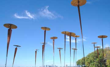 A photo of an outdoor art installation of metal poles with metal cymbols on top. A blue sky is in the background.