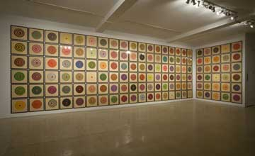An art installation featuring a series of two walls filled with square tiles with circles of colour in the centre of each.