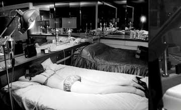 A black and white photo of a room with two beds and a woman in underwear and heels lying face down on a bed.