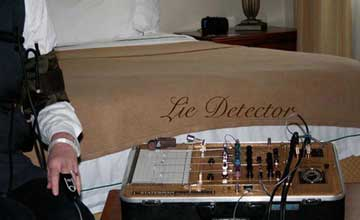 A man's arm is strapped to a lie detector in front of a hotel bed with lie detector embroidered onto the blanket.