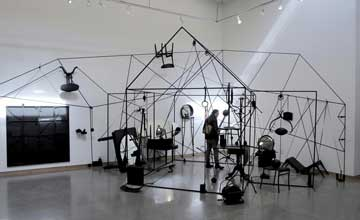An art installation featuring slim black poles to create the outline of a house-like structure. Black household furniture hangs from and is scattered around the installation.
