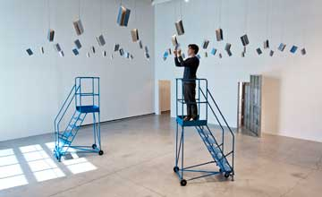An art installation featuring hanging books and two blue rollings stairs with a person standing on one.
