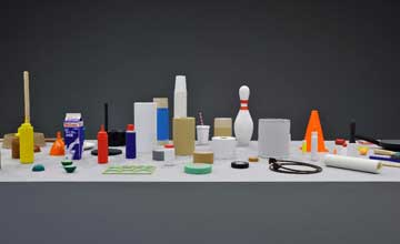An art installation featuring an assemblage of small household and other items on a white table.
