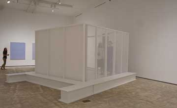 An art installation in a white room with a small structure in the centre. You can see people behind one semi-transparent wall of the structure.