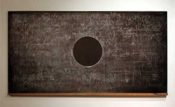 An art installation with a chalkboard hanging on a white wall. The chalkboard is filled with partially erased formulas except for a single clean circle in the centre.