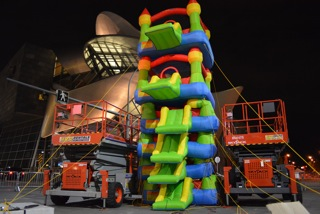 An art installation with two scissor lifts on either side of a pile of stacked bouncy castles.