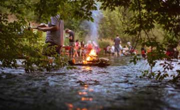 A group of people standing in a river with a small burning pyre in the centre.