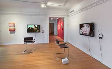 An art installation featuring a white room with two flat screen televisions hung in front of chairs.