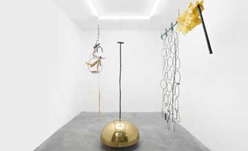 An art installation featuring three metal sculptures in a white room.
