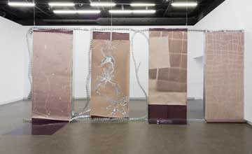 An art installation featuring four brown textured hangin panels.