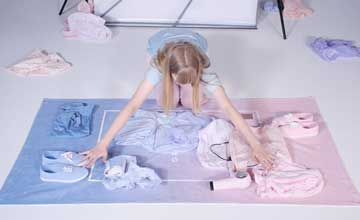 An image of a woman kneeling over an arrangement of purple and pink pastel garments.