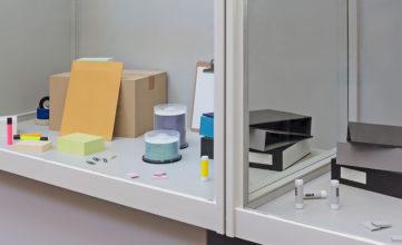 Office supplies artfully arranged on a shelf.