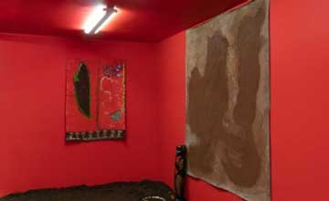 An art installation featuring a red room with a carved figure and textile wall hangings.