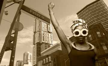 A sepia photo of a woman with raised arm standing in front of Toronto buildings