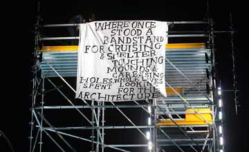 A image of a metal structure with hanging banner of text