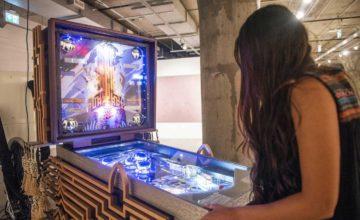 An image of a woman playing a pinball machine