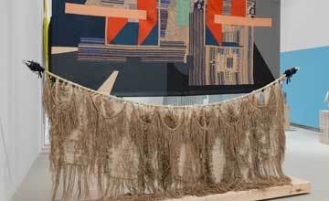 A mixed textile art installation of a wall hanging with geometric shapes and a fishing net.